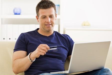 outwork: El hombre de la casa de compras en l�nea usando tarjetas de cr�dito y computadora port�til.