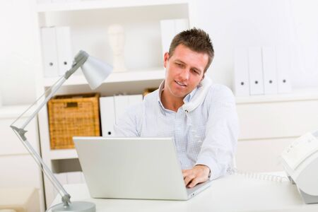 small office: Business man working on laptop computer at home.