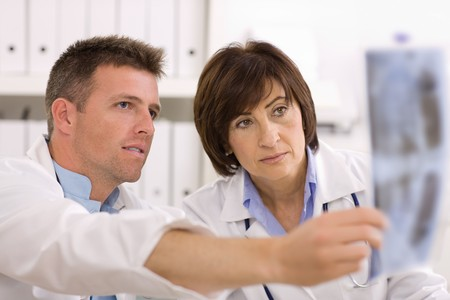 Doctors coworking looking at x-ray image at office. Stock Photo - 4175683