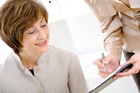 color consultant: Happy senior businesswoman reviewing documents at office, smiling.