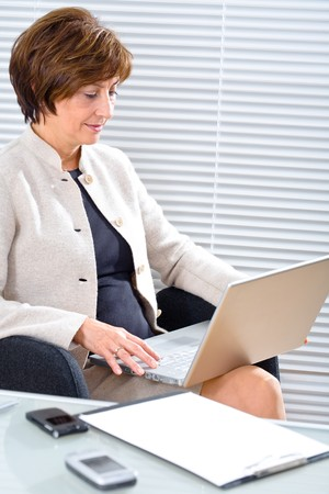 Senior businesswoman working in office, using laptop. photo