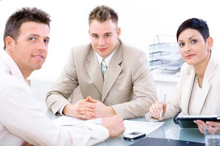 businessteam: Businessteam of three working together, sitting around a desk, looking at camera. Stock Photo