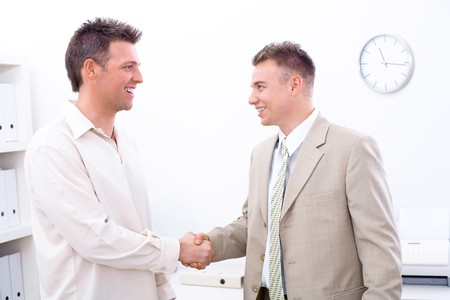 Two businessmen shaking hands in office, smiling. photo