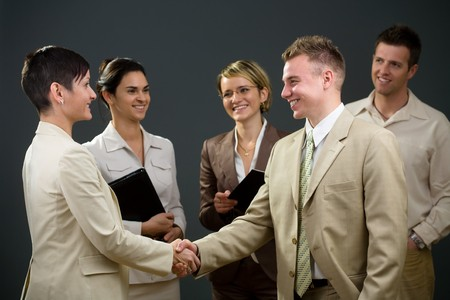 Businessman and businesswoman shaking hands in front of smiling colleagues.
