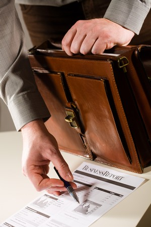 Business man opening elegant brown leather briefcase and showing printed business report. photo