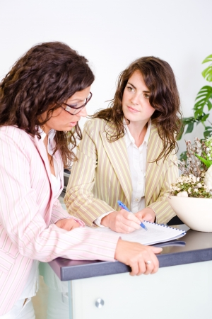 Casual businesswomen working together in team at office reception, looking at documents, talking. Stock Photo - 4193367