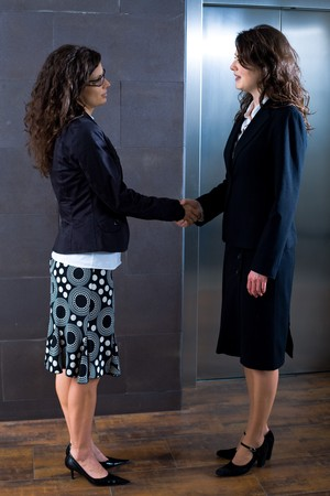 Smiling businesswomen shaking hands at office lobby in front of elevator. Stock Photo - 4193376