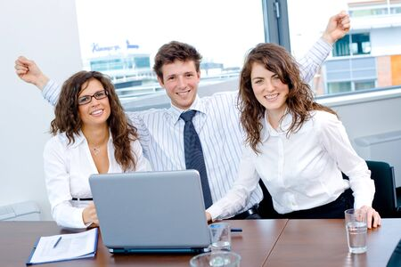 Happy successful business people sitting on meeting at office, working on laptop computer, smiling. Stock Photo
