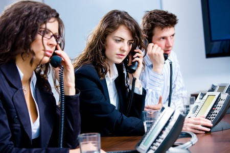 businesswear: Young customer service operator team working at office, holding phone, calling, giving helpdesk support. Stock Photo