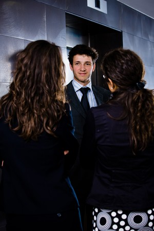 Happy young businessman businesspeople talking to business people on office corridor in front of elevators. Stock Photo - 4193364