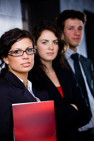 Portrait of successful happy business team posing at office lobby in front of elevator. Dark background. Stock Photo - 4193363