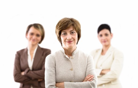 Happy businessteam of three businesswomen standing in front of windows inside officebuilding, smiling, senior businesswoman leading. Isolated on white. photo