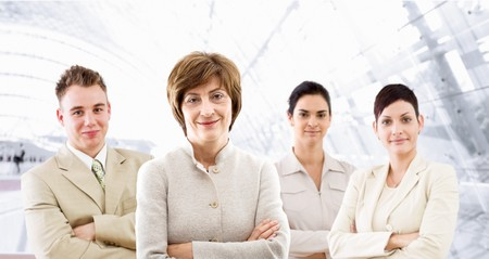 businessteam: Happy businessteam posing in front of windows inside officebuilding, smiling.   Stock Photo