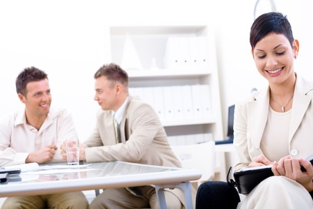 Businessteam of three working at office, businesswoman sitting in foreground, making notes, smiling. photo