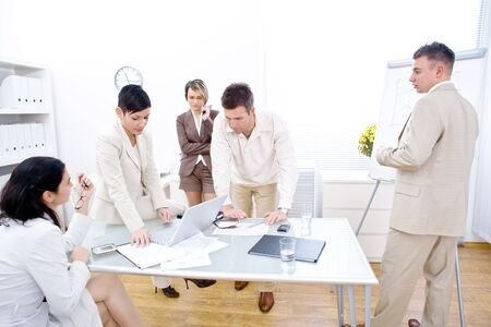 Five business people working together in office. Three woman and two man. One sitting, one standing, one sitting on desk, one leaning on desk, while the last one writing on whiteboard.