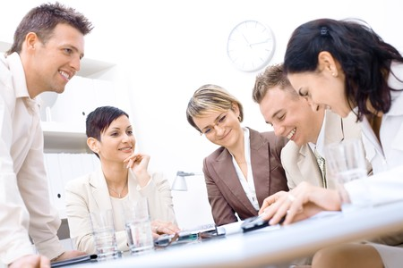 businessmeeting: Five business colleagues sitting around table and working together, smiling.