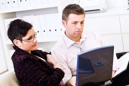 Troubled businessman and female assistant working on a laptop computer at office. photo