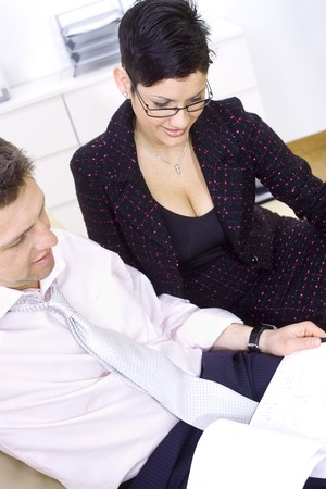stitting: Businesspeople working together, stitting on couch looking at business report, smiling. Stock Photo
