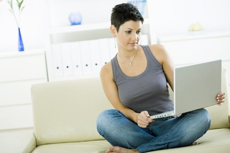 Young woman sitting on sofa at home working on laptop computer. Stock Photo - 4204765