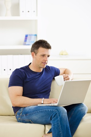 Man sitting on sofa at home and using laptop computer. photo