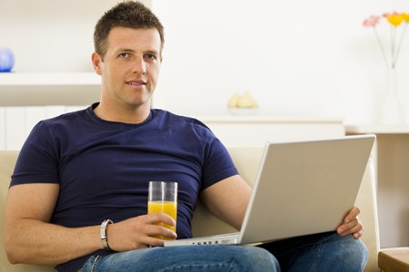 Man sitting on sofa at home and using laptop computer. Stock Photo - 4204759