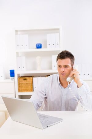 Business man working on computer at home calling on phone. Stock Photo - 4204748