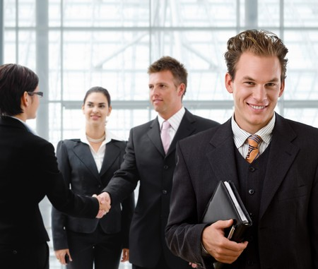 Team of business people, businessman in front, handsake in background. Stock Photo - 4204773