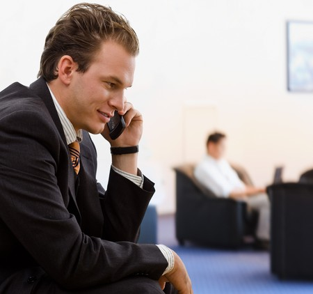 Businessman calling on mobile phone at office lobby, smiling. Stock Photo - 4204743