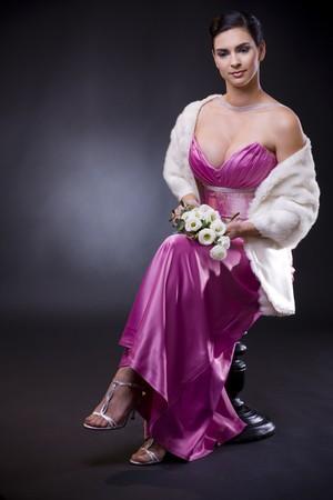 estola: Joven y bella mujer sentada en una silla llevando p�rpura vestido de noche con la piel blanca robaron, la celebraci�n de bouqet de rosas blancas.