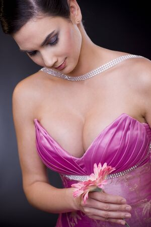 Beautiful young woman wearing purple evening dress holding a flower and daydreaming. photo