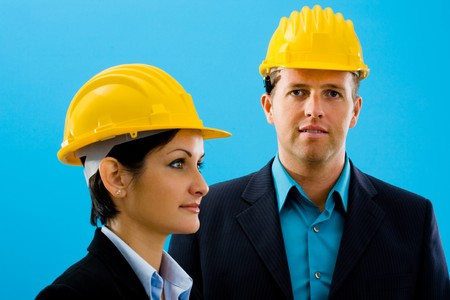 Young architects in yellow hardhat against blue background. Stock Photo - 4204757