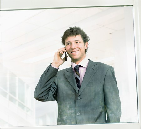Young successful businessman talking on cellphone in office window, smiling. photo