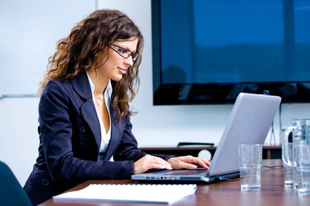 Young happy businesswoman working on laptop computer in meeting room at office, smiling. photo