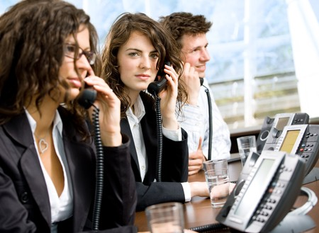 Young and happy customer service operators sitting in a row and calling on landline phones.  Stock Photo