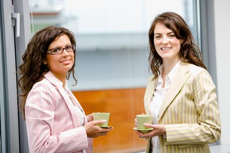 Happy young businesswomen having break at office drinking coffee, looking at camera, smiling. Stock Photo - 4204841