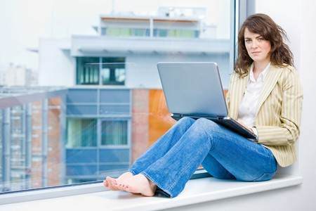 Young businesswoman sitting at office window, thinking and working on laptop computer. photo