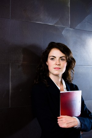 Young businesswoman in dark suit holding red folder daydreaming on office corridor posing for business portrait. photo
