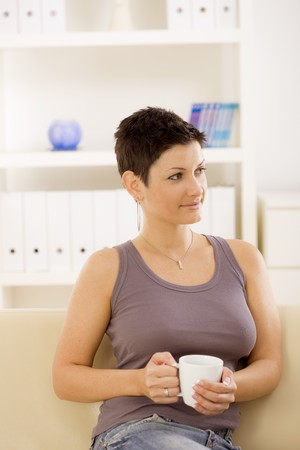 Young woman sitting on sofa at home, drinking coffee. photo