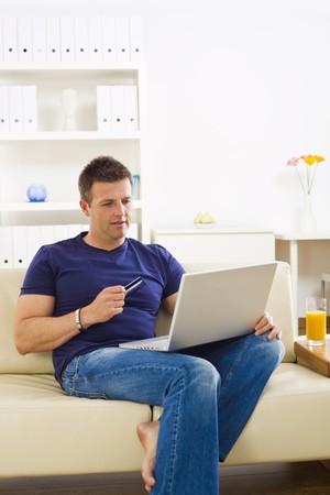 orden de compra: El hombre de la casa de compras en l�nea usando tarjetas de cr�dito y computadora port�til.