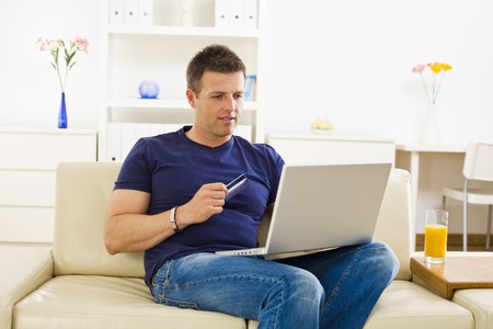 sinecure: Man shopping online from home using credit card and laptop.