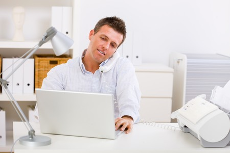Business man working on computer at home calling on phone. Stock Photo - 4204796