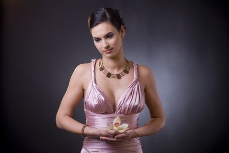 formal attire: Studio portrait of a beautiful young woman wearing evening dress, holding orchid flower in her hand.
