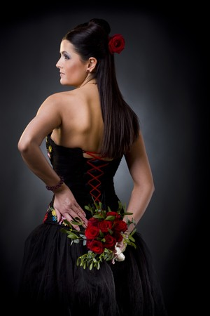 Beautiful young woman posing in a black cocktail dress holding a bouqet of red roses. photo