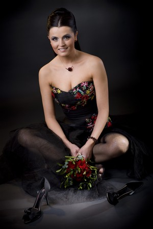 Beautiful young woman wearing a black cocktail dress sitting on the floor with her shoes removed. photo