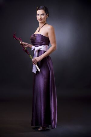 Studio portrait of a beautiful young woman wearing a light purple evening dress holdiing flowers in her hands. Stock Photo