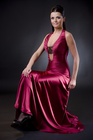 Attractive young woman sitting on a chair wearing low cut evening dress.