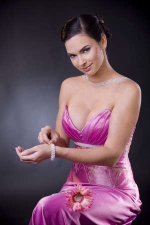 Beautiful young woman sitting on a chair wearing purple evening dress adjusting her bracelet, smiling and looking at camera. photo