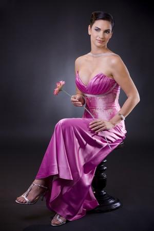 Joven y bella mujer sentada en una silla llevando púrpura vestido de noche la celebración de una flor.