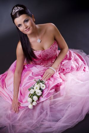 Happy young bride posing in a pink wedding dress, holding bouqet of white flowers. Stock Photo - 4204844
