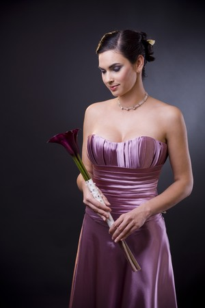 Studio portrait of a beautiful young woman wearing a light purple evening dress holdiing flowers in her hands. photo